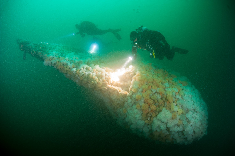 Foto: Cor Kuyvenhoven Beschrijving: Drie duikers die een Russische onderzeeer onderzoeken die in de jaren negentig is gezonken toen deze bij zwaar weer versleept werd over Nederlands grondgebied.